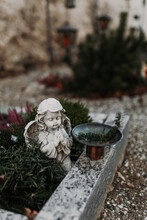 Angel Statue Decorating Old Grave And Twig Used As Aspersorium To Sprinkle Holy Water In Tiny Mountain Cemetery