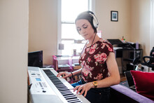 Woman Playing Piano Keyboard At Home