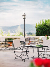 Garden Chairs And Tables On Terrace Decorated With Flowering Plants In Bright Sunny Day