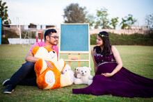 Young Pregnant Asian Indian Couple Looking At Each Other Sitting In A Garden With Lots Teddy Bear Toys And Blank Chalkboard To Write Message. Pregnancy Concept.