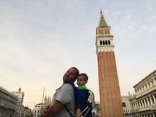 Portrait Of Father With Son Standing By St Mark Campanile On Street Against Sky