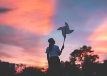 Young Woman Holding Pinwheel Toy While Standing Against Sky During Sunset
