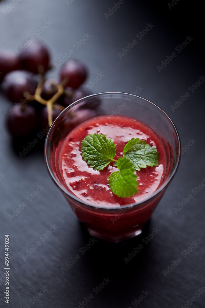 Fototapeta Fresh smoothie in a glass. Dark background. Close up.