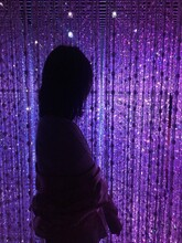 Side View Of Woman Standing Against Purple Decoration