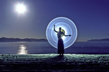 Young Woman Posing Against Light Painting At Beach