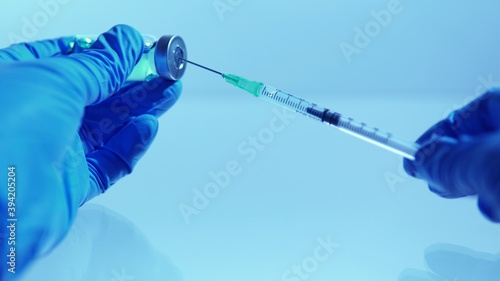Leinwand Poster Hand of scientists in blue gloves holding vial with safe and effective vaccine against virus