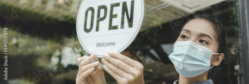 Fototapeta wide banner. waitress wearing protection face mask turning open sign board on glass door in modern cafe coffee shop, cafe restaurant, retail store, small business owner, food and drink concept obraz