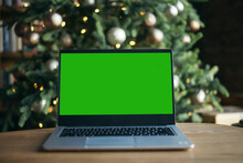 Front View Of Laptop With Green Screen On Christmas Tree Background. Help With New Technologies. Isolation At Home According To The Concept Of Coronavirus. Freelance. Copy Space