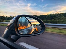 Close-up Of Side-view Mirror Against Sky At Sunset