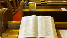 High Angle View To Holy Bible On Pew In Church