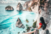 Traveler Woman Look At The Ocean And Rocks. Travel And Active Lifestyle Concept. Adventure And Travel On Bali, Indonesia.