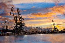 Sea Cargo Port At Sunset. Sea Cargo Terminal. Port For Loading Ships. Ship Port On A Summer Evening. Loading Cranes At The Seaport. Two Tower Cranes For Loading Onto A Ship Nearby.