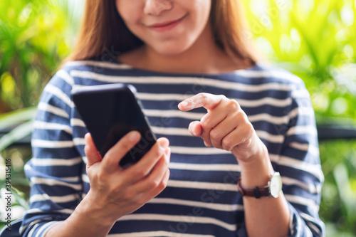 Fototapeta Closeup image of a beautiful young asian woman holding and using smart phone obraz