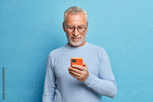 Cuadros en Lienzo Photo of satisfied bearded man focused in smart phone surfs internet sends text messages in social networks uses modern technologies wears casual blue jumper poses indoor