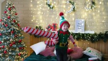 Little Cheerful Boy In An Elf Hat Jumping On The Bed With An Inflatable Cane In His Hands