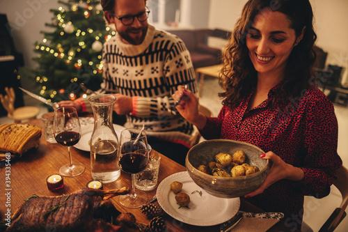 Obraz Couple enjoying Christmas dinner at home - fototapety do salonu