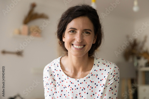Fototapeta Close up headshot portrait of smiling young Caucasian woman look at camera pose in flat apartment. Profile picture of happy millennial female renter or tenant feel satisfied excited show optimism. obraz