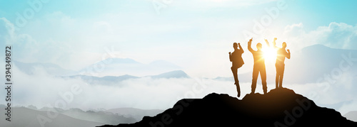 Fototapeta Silhouette of Business team show arm up on top of the mountain. Leadership and success Concept. obraz