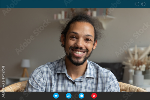 Computer application display head shot view smiling young african american man holding video call distant conversation with friend, looking at web camera or passing remote job interview at home.