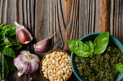 Flat lay food background of genovese pesto sauce and its ingredients on wooden kitchen table with copy-space