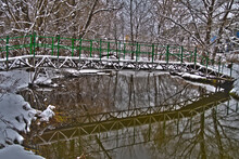 Footbridge With Blue Metal Railings Across A Narrow River Surrounded By Snow-covered Trees