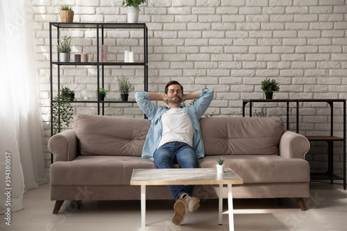Fotografie, Obraz Peaceful young man relaxing meditating on comfortable sofa with folded hands beh