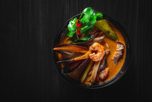 Pan Asian Food. Tom Yum Soup In Black Bowl On Black Wooden Table Background