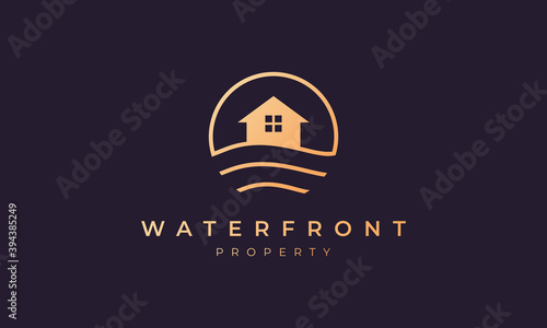 Fotografia, Obraz real estate agency logo of gold line with house in circle shape with ocean wave