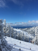 Vertical View Of Skiers On A Ski Slope At A Resort In Winter On A Sunny Day With Blue Skies, ,with Lake Tahoe In The Background