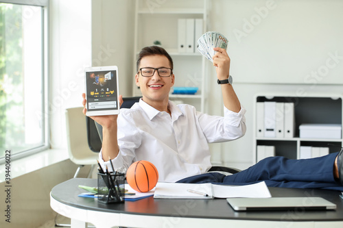 Canvas Print Young businessman placing sports bet in office