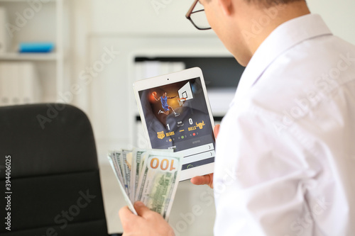 Fototapeta Young businessman placing sports bet in office