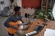 Leinwandbild Motiv High angle portrait of young African-American man playing guitar and singing to microphone in home recording studio, copy space