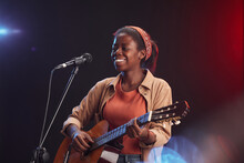 Waist Up Portrait Of Young African-American Woman Playing Guitar On Stage And Singing To Microphone Smiling, Copy Space