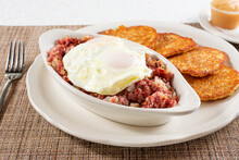 A View Of A Casserole Dish Of Corned Beef Hash, Topped With A Over Easy Eggs.