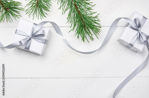 Tela Christmas gift boxes with pine tree branches on white wooden background