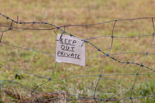 Keep Out, Private Sign Fixed To Barbed Wire Fence