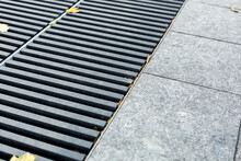 Grating Of The Drainage Storm System On The Pedestrian Park.sidewalk Made Of Gray Stone Granite Tiles And An Iron Storm Cover With Autumn Yellow Leaves On The Floor, Nobody.
