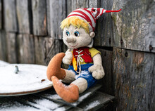 Abandoned Old Dirty Toy Smiles Despite The Sad Situation. The Concept Of Loneliness And Uselessness.