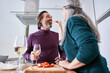 Leinwandbild Motiv Woman feeding with cheese brie her unshaven husband