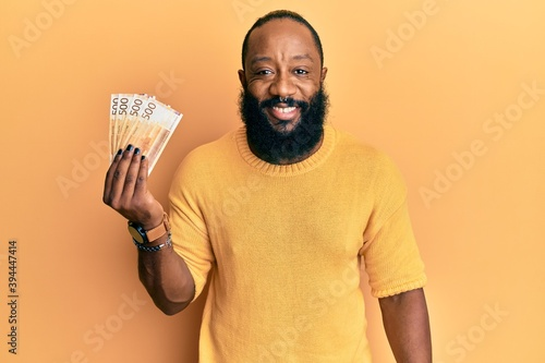 Fototapety, obrazy: Young african american man holding 500 norwegian krone banknotes looking positive and happy standing and smiling with a confident smile showing teeth