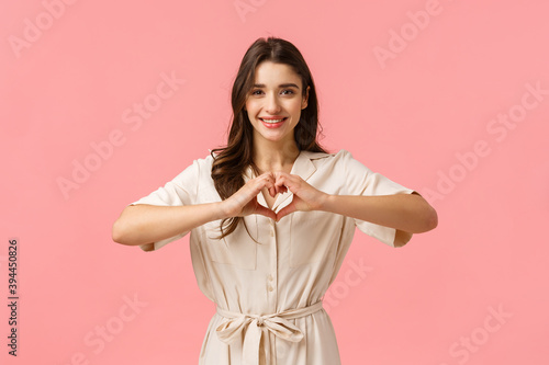 Photo Waist-up portrait charming young brunette girl in dress, showing heart sign with