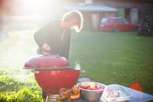 Woman Having Grill In Garden, Sweden