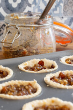Mince Pies In A Baking Tray With Mincemeat In A Clip Glass Jar And A Spoon.  On A Wood Worktop With A Tiled Background