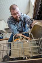 Man Putting Dishes Into Dishwasher, Sweden