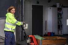 Woman Pushing Pallet Truck, Sweden