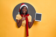 A Young  Woman In A Santa Claus Hat And Red Scarf Smiles And Points To A Tablet With Empty Space. Discounts, Gifts, Benefit Concept.