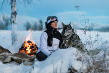 Woman With Dog Sitting At Camp Fire, Sweden