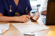 Nurses Hand Holding Pill Bottl...