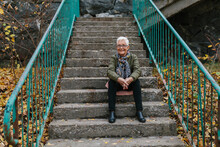 Senior Woman Sitting On Stairs...