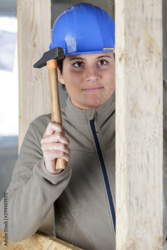 Fototapeta joyful builder smiling and hammering a nail into the wall